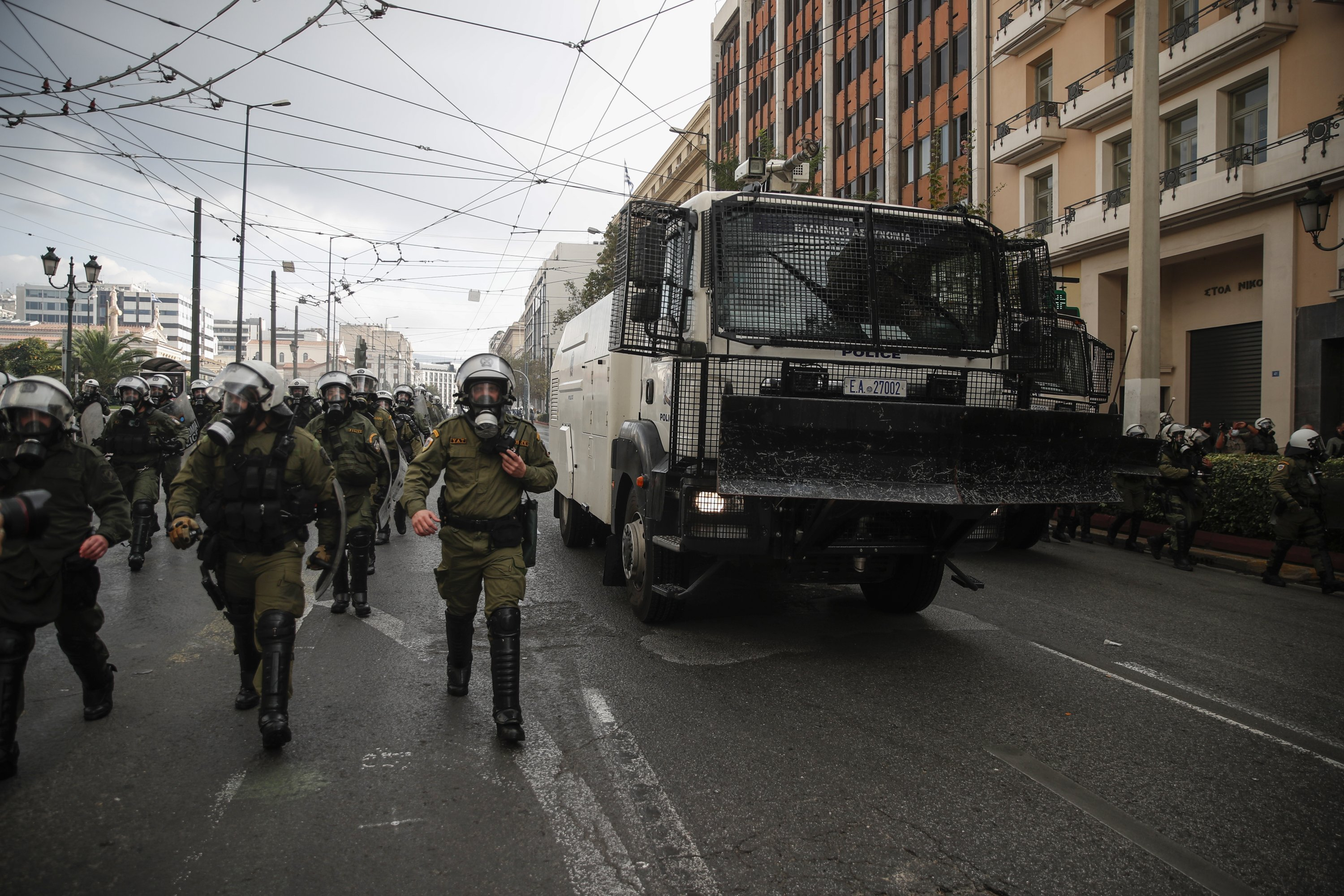 Riot Police officers walk next to a water cannon vehicle, in central Athens, Nov. 17, 2020. Thousands of police officers have been deployed in Athens and the northern Greek city of Thessaloniki to prevent gatherings usually held to mark the anniversary of the 1973 crushing of a student uprising against the military junta then ruling Greece. The government has banned the marches this year, citing public health concerns as the country struggles to contain a resurgence of the coronavirus. (AP Photo/Thanassis Stavrakis)