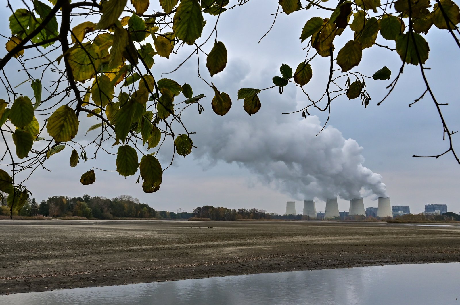 Behind a drained carp pond, water vapour from the cooling towers of the Jänschwalde lignite-fired power plant of Lausitz Energie Bergbau AG (LEAG) rises into the cloudy autumn sky. (Getty Images)