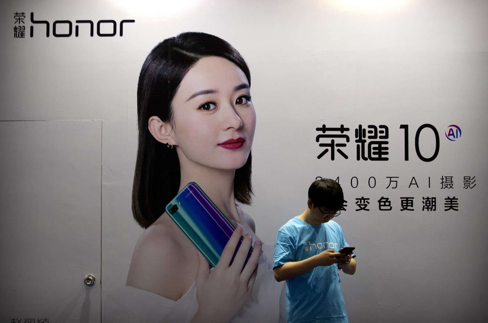 A staff member uses his smartphone in front of a billboard for Chinese smartphone brand Honor at the Global Mobile Internet Conference in Beijing, China, April 26, 2018. (AP Photo)