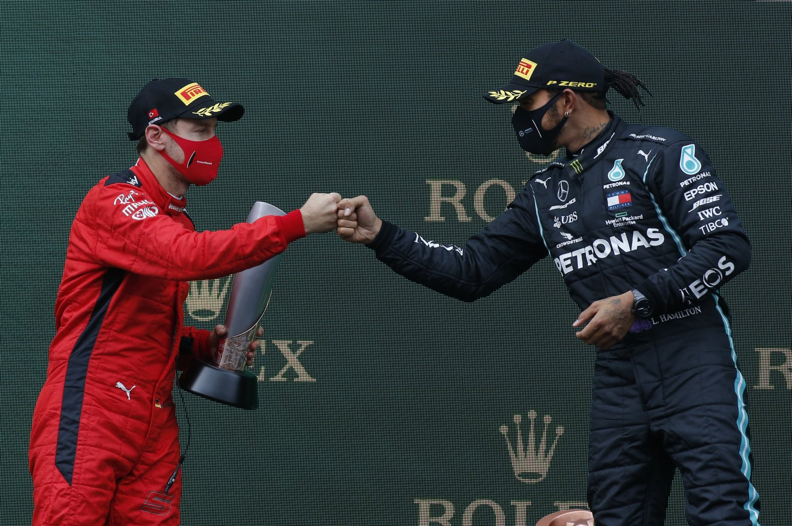 Ferrari driver Sebastian Vettel (L) and Mercedes driver Lewis Hamilton bump fists after the Formula One Turkish Grand Prix in Istanbul, Turkey, Nov. 15 , 2020. (AP Photo)