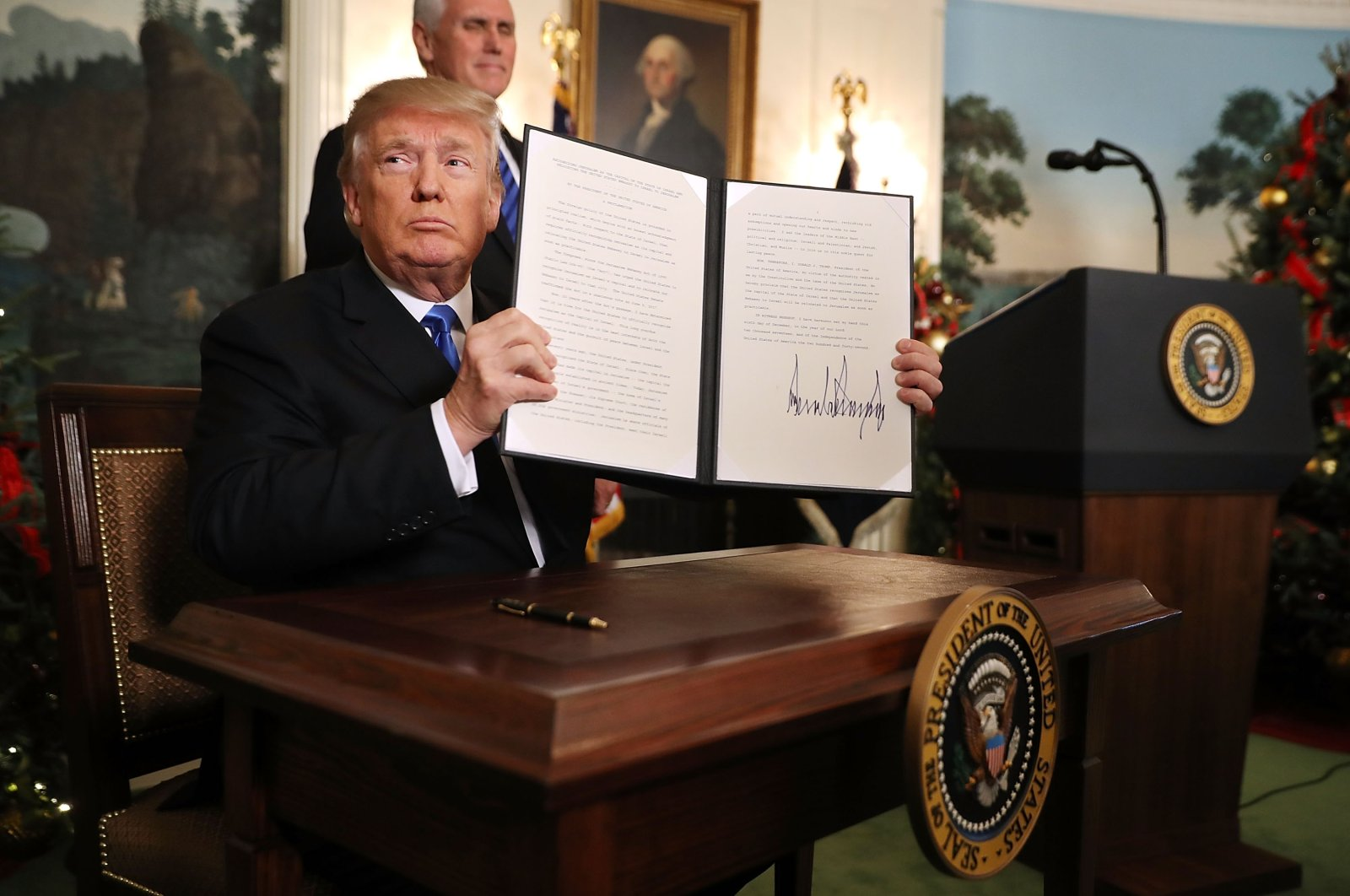 U.S. President Donald Trump holds up a controversial proclamation that the U.S. will formally recognize Jerusalem as the capital of Israel after signing the document at the White House, Washington, D.C., Dec. 6, 2017. (Photo by Getty Images)