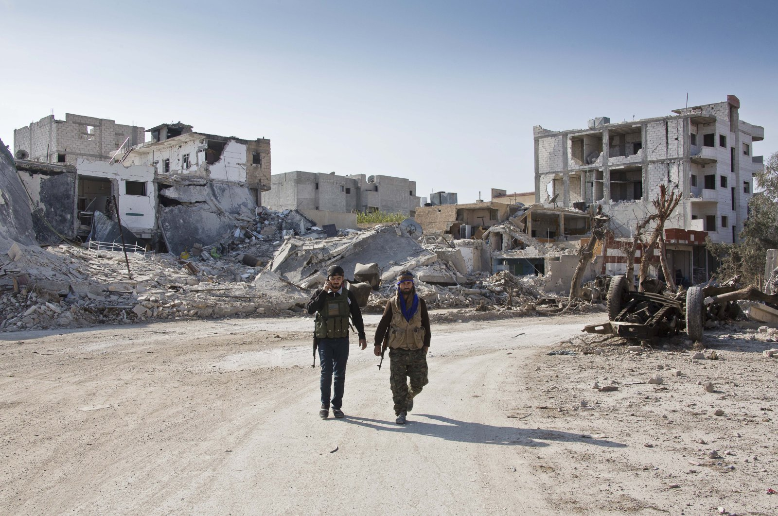 YPG terrorists walk near the town entrance circle heading to their strongholds in Ayn al-Arab, Syria on Nov. 19, 2014. (AP File Photo)