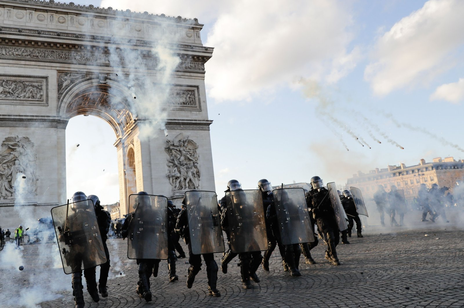 Riot police officers charge using tear gas canister at the Arc de Triomphe on the Place de l'Etoile, Paris, March 16, 2019. (AFP Photo)