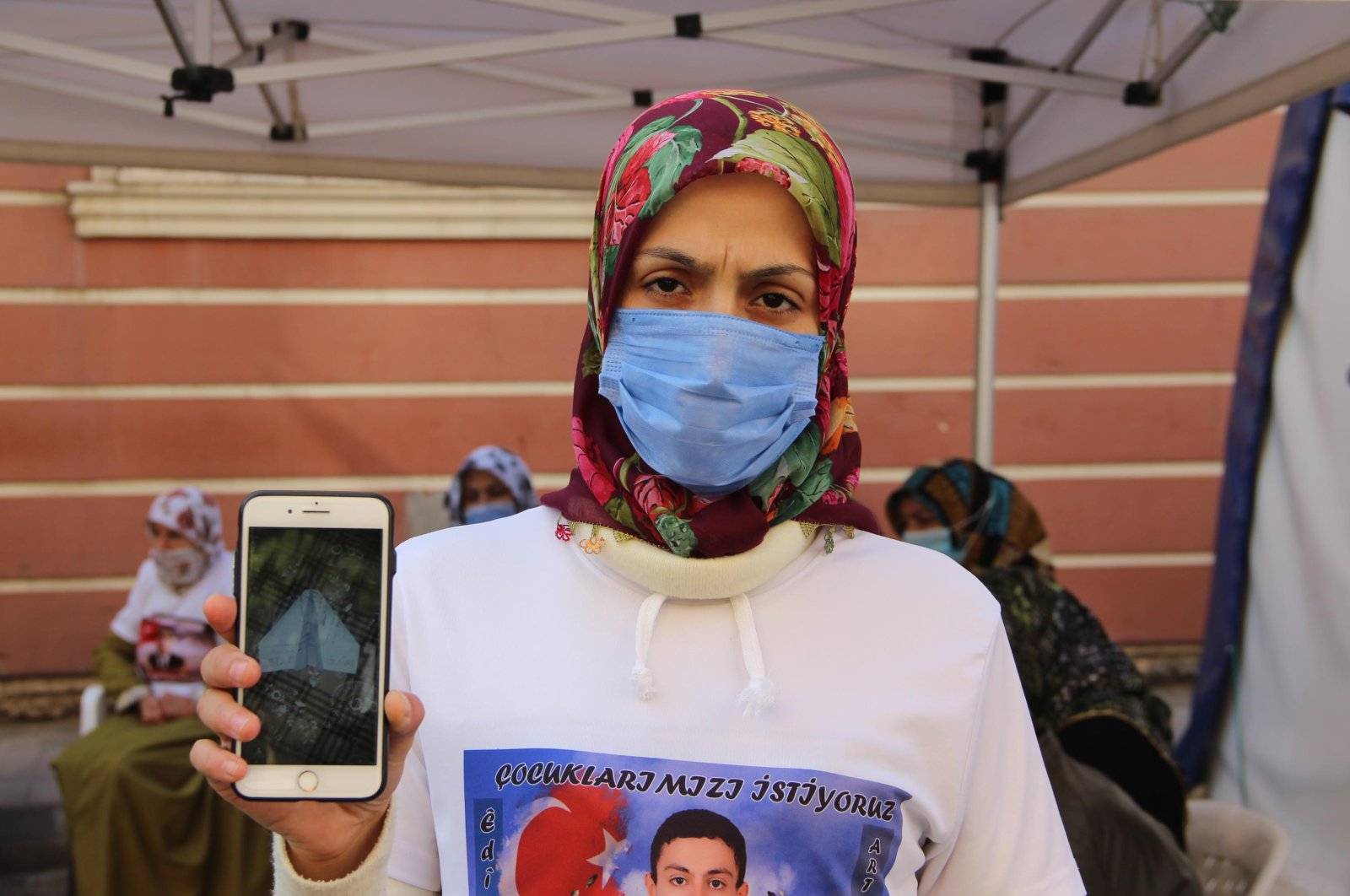 Ayşegül Biçer shows the picture of the death threat sent to her home by the PKK terrorists on her phone while wearing a t-shirt with a picture of her abducted child, Mustafa, Diyarbakır, Turkey, Nov. 17, 2020. (DHA)