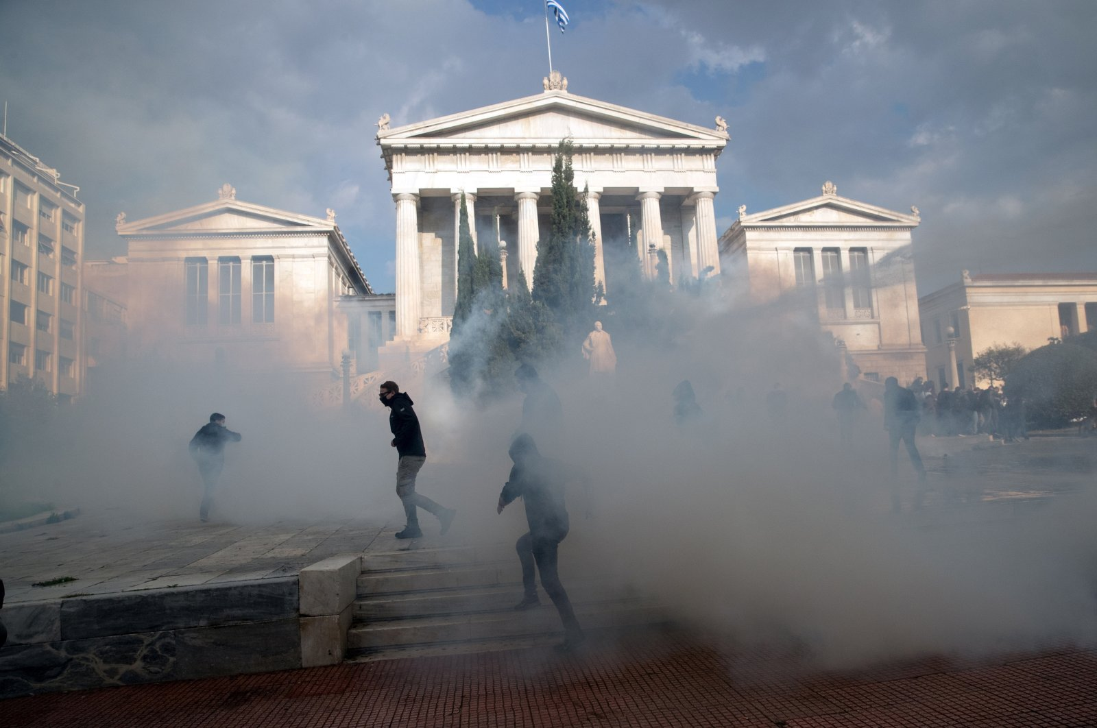 Members of the Greek Communist Party (KKE) flee tear gas and a water cannon during clashes with riot police, as the Greek government banned the annual march to mark the anniversary of a 1973 student revolt against the then military junta due to coronavirus, in Athens, Greece, Nov. 17, 2020. (Reuters Photo)