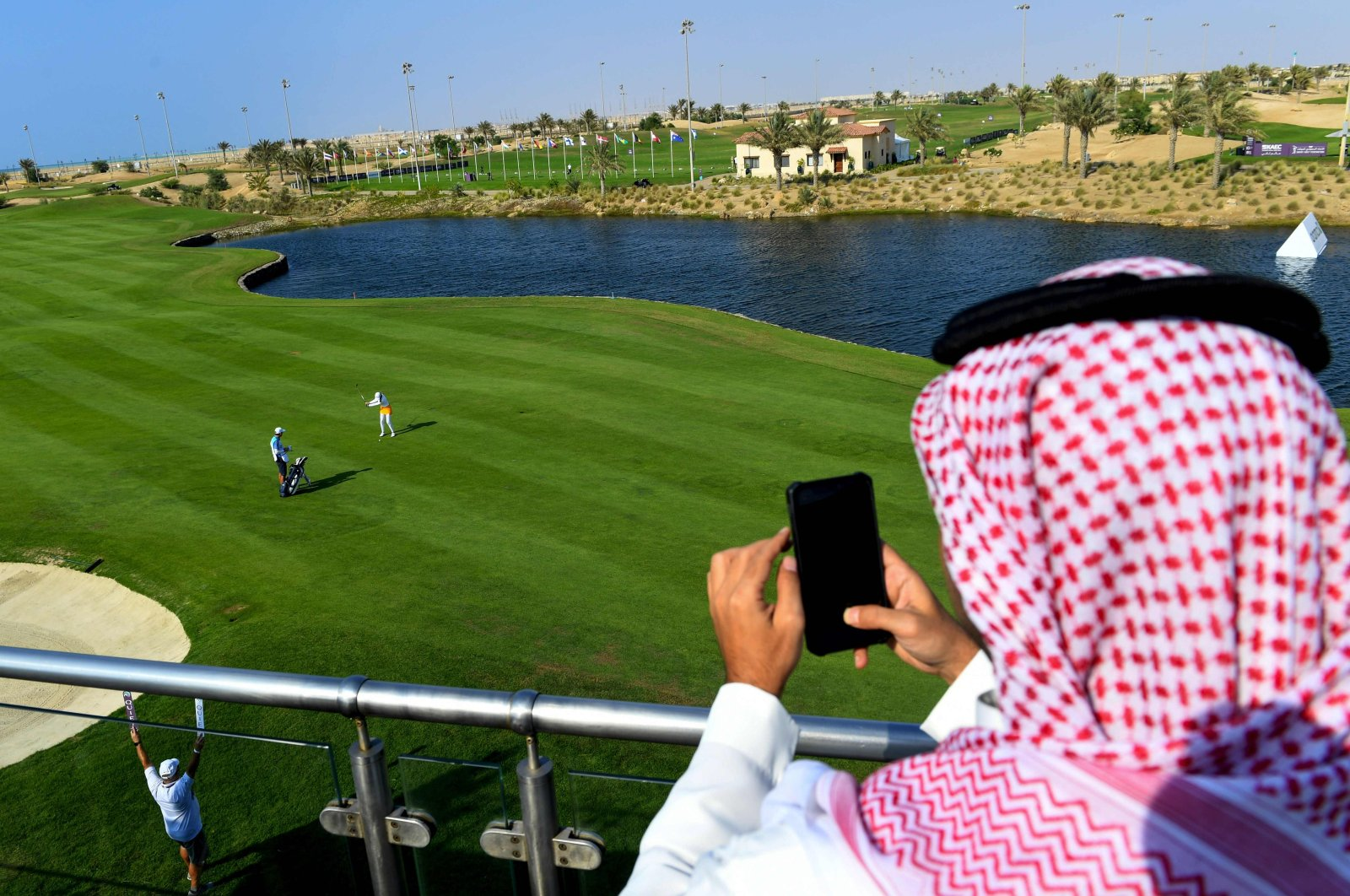 A Saudi man watches a golfer compete in the Saudi Ladies International golf tournament at the King Abdullah Economic City, north of Jeddah, (AFP Photo)