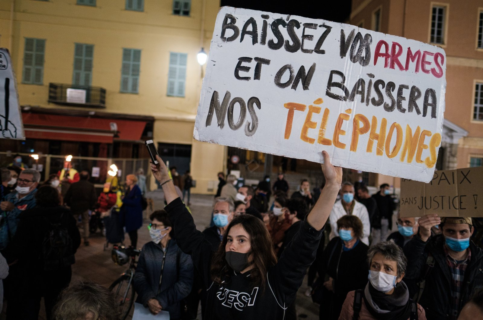 """Demonstrations protesting the global security law in front of the courthouse in Nice, Nov. 17, 2020. The sign says """"Lower your weapons and we will lower our phones."""" (Jean Baptiste Premat / Hans Lucas via Reuters)"""