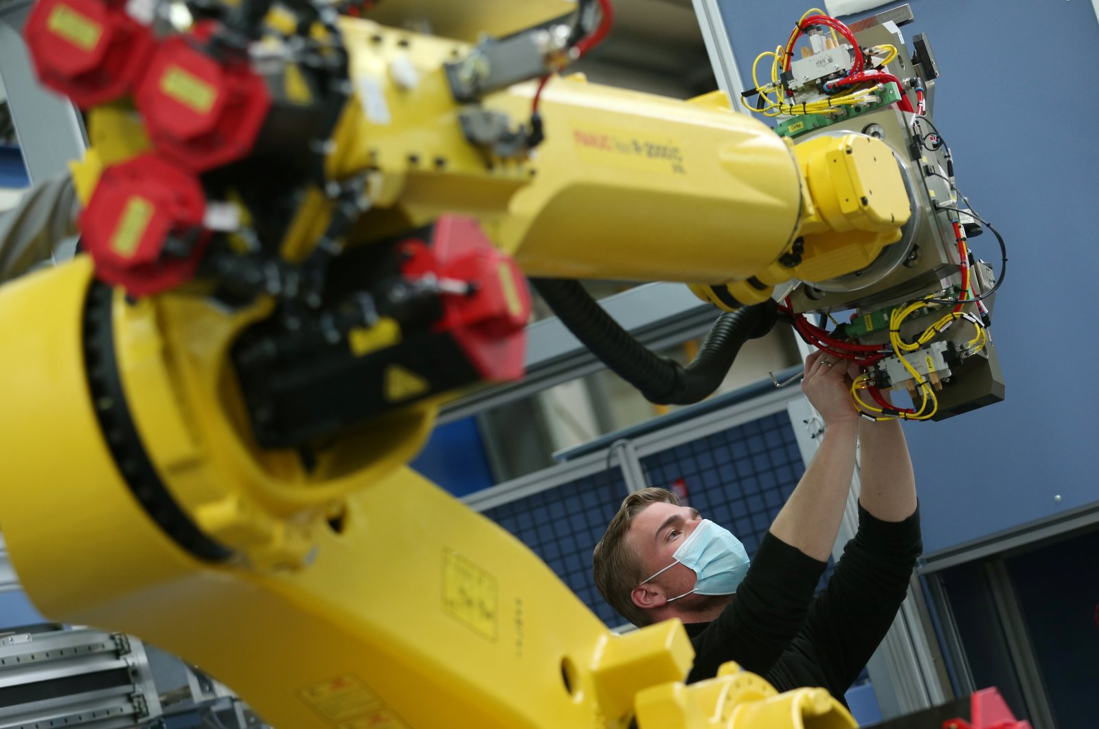 An employee works on an industrial robot at HAHN Automation company in Rheinboellen, Germany, Nov. 11, 2020.  (Reuters Photo)