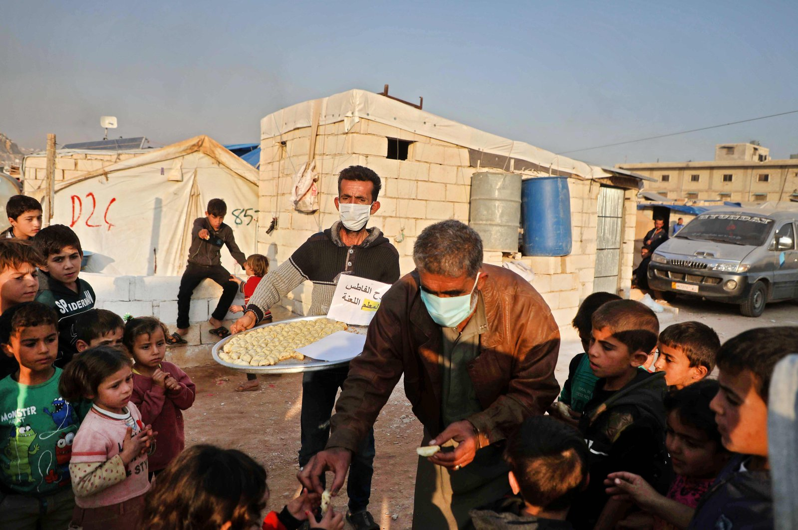 Men distribute traditional desserts to children at a camp for displaced Syrians in Kafr Dariyan, in the north of Syria's northwestern Idlib province, Nov. 16, 2020. (AFP Photo)