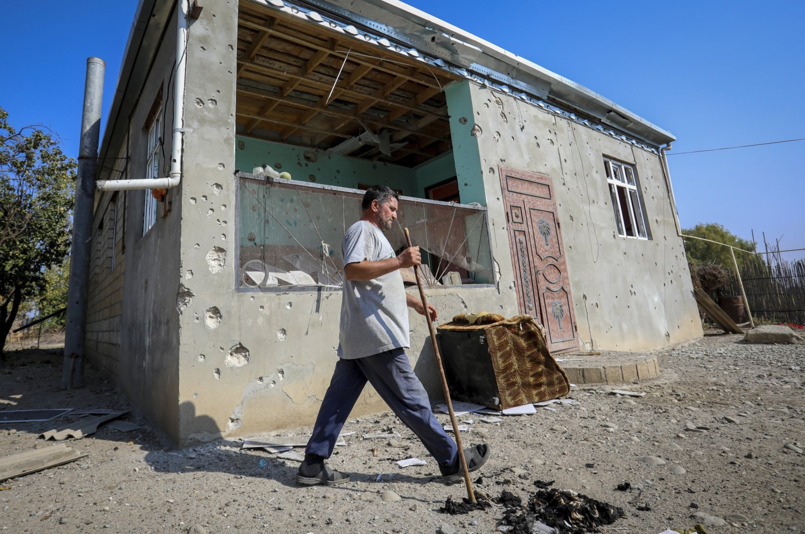 A man walks past a house damaged by shelling during fighting over the region of Nagorno-Karabakh in Aghdam, Azerbaijan, Oct. 19, 2020. (AP Photo)
