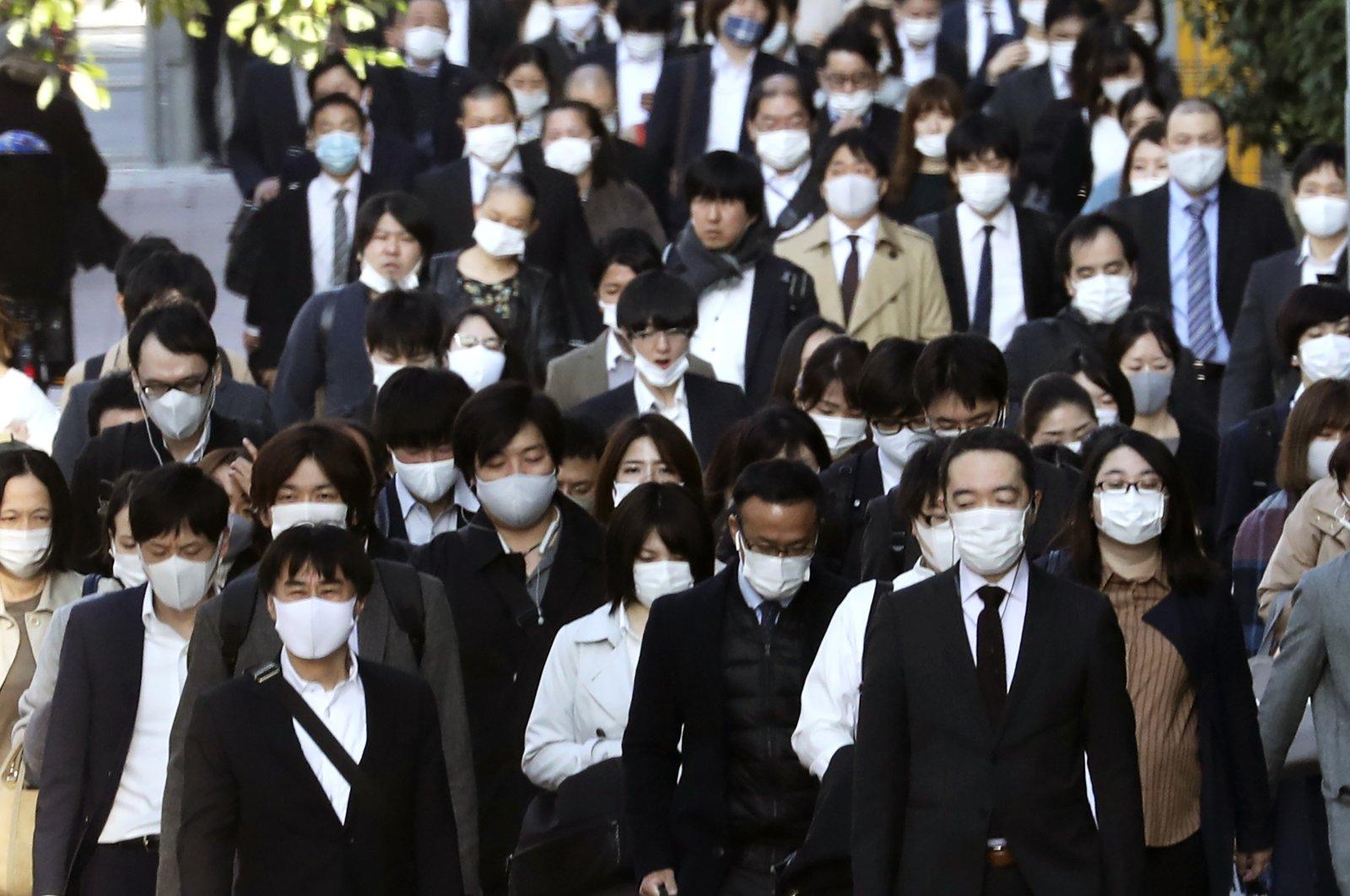 Commuters wearing masks walk on a street in Tokyo, Japan, Nov. 17, 2020. (AP Photo)