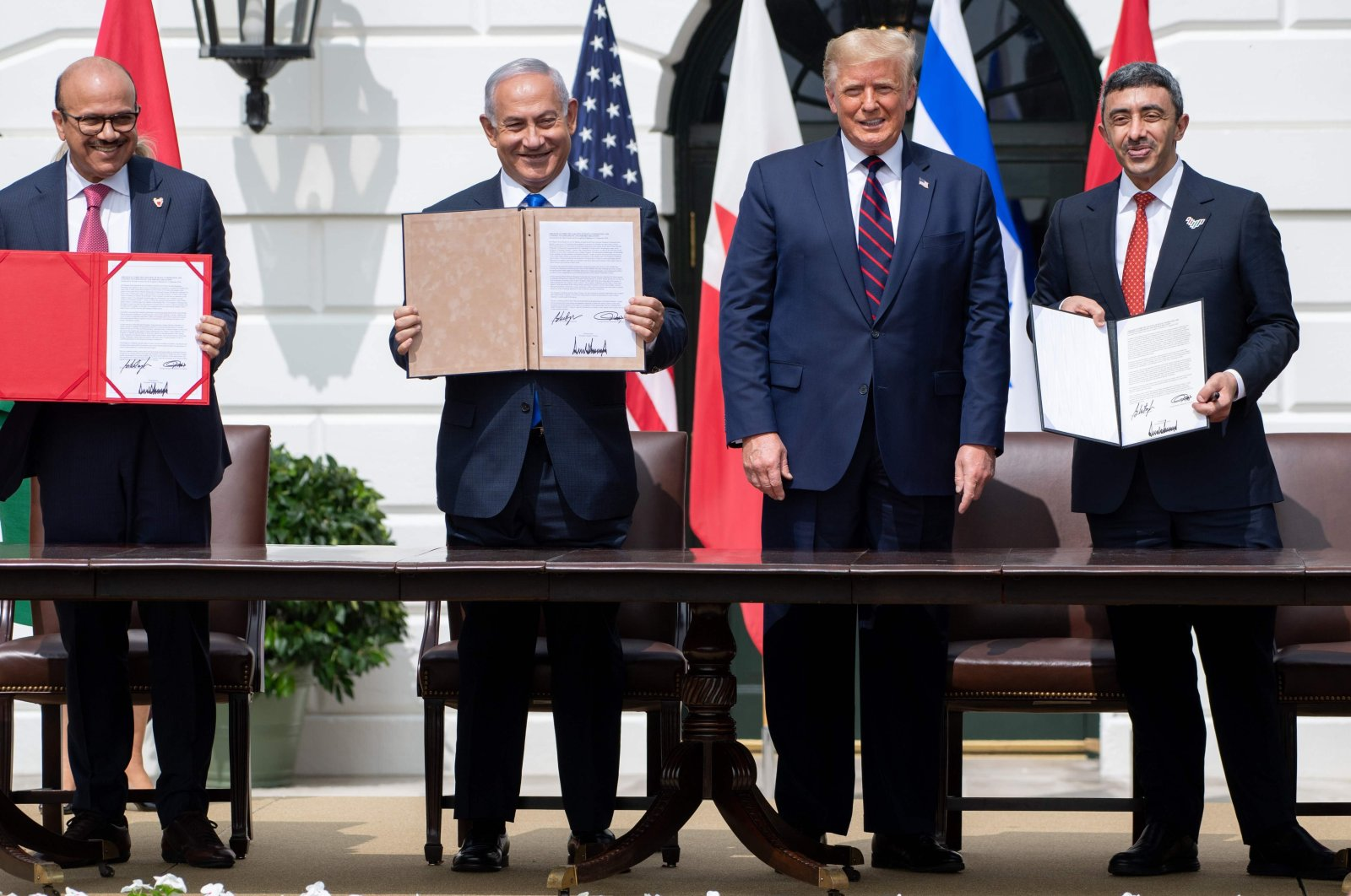(L-R) Bahrain Foreign Minister Abdullatif bin Rashid Alzayani, Israeli Prime Minister Benjamin Netanyahu, U.S. President Donald Trump, and UAE Foreign Minister Abdullah bin Zayed Al Nahyan hold up documents after participating in the signing of the Abraham Accords, Washington, D.C., Sept.15, 2020. (AFP Photo)