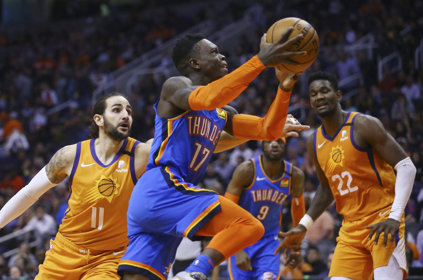 Oklahoma City Thunder's Dennis Schroder (C) drives past Phoenix Suns' Ricky Rubio (L) during an NBA game in Phoenix, U.S., Jan. 31, 2020. (AP Photo)
