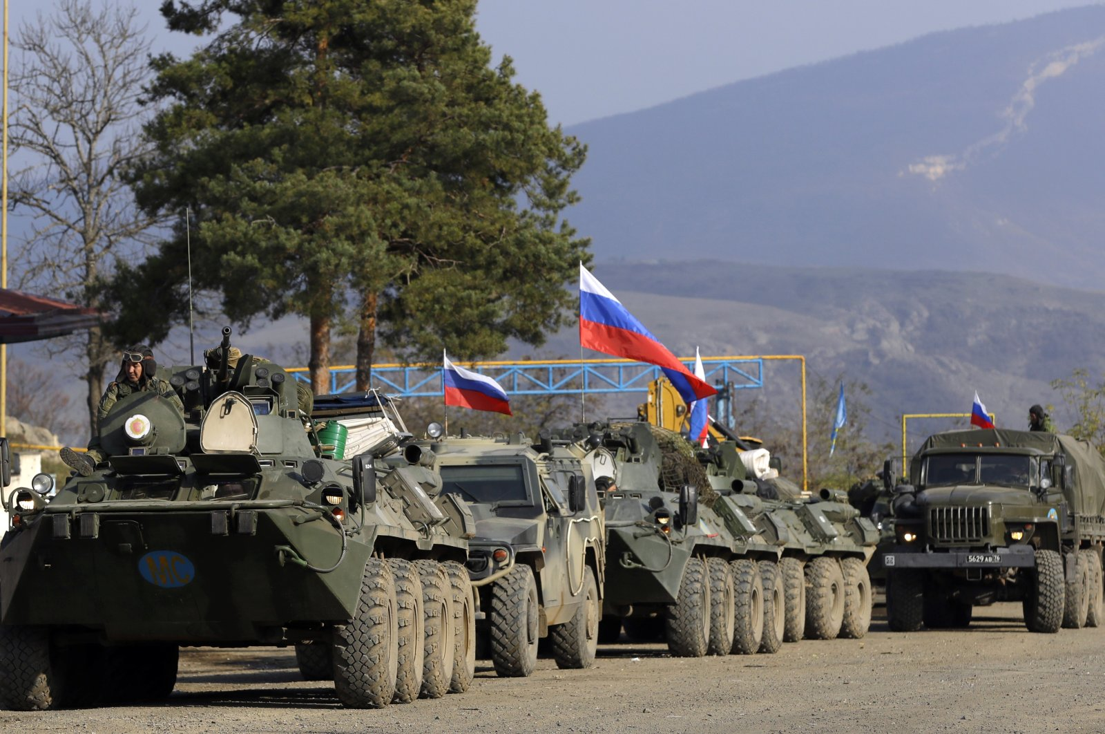Russian peacekeepers' military vehicles with Russian national flags parked at a checkpoint on the road to Shusha in the region of Nagorno-Karabakh, Nov. 17, 2020. (AP Photo)