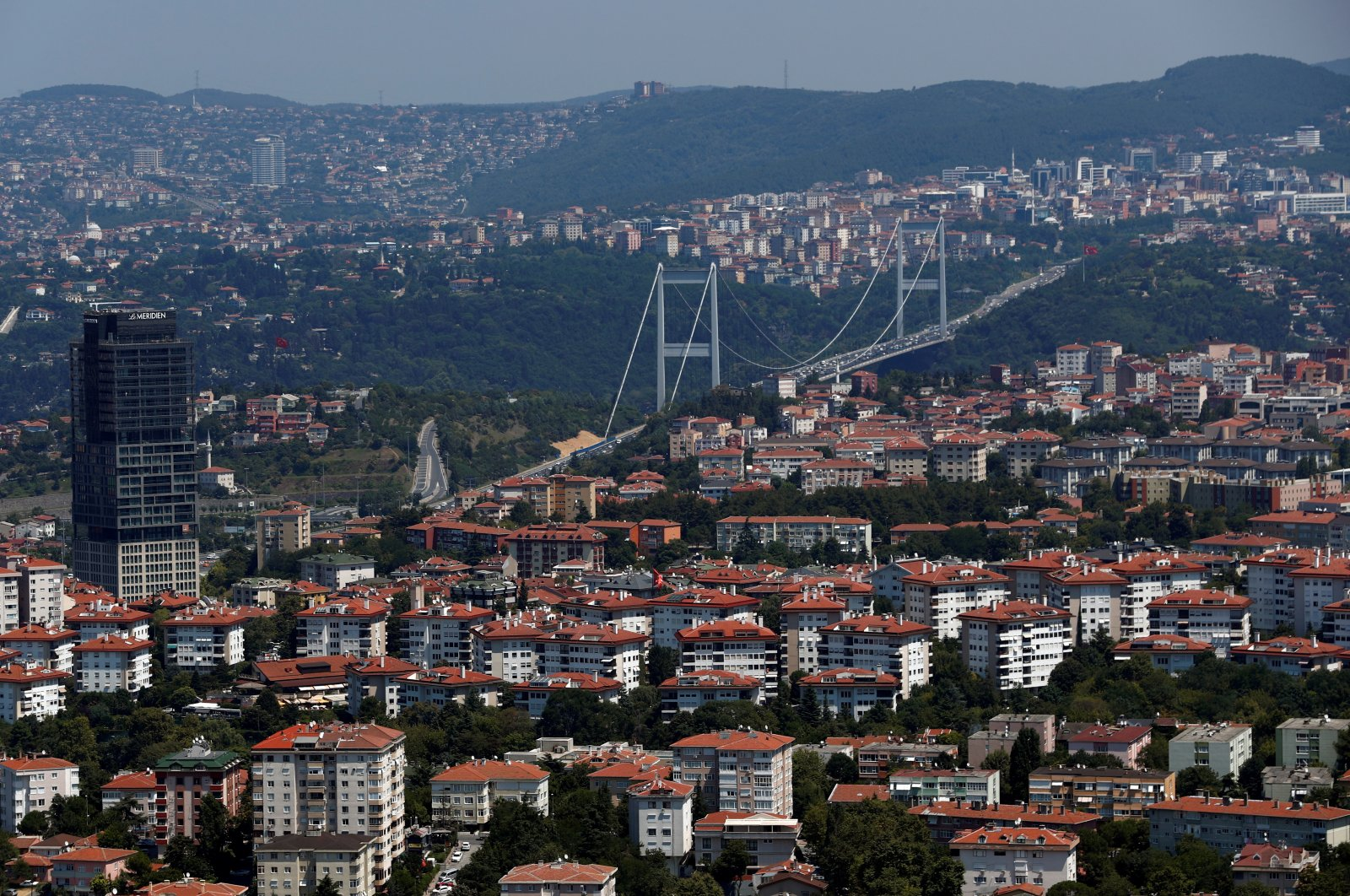 The Fatih Sultan Mehmet Bridge linking the city's European and Asian sides over the Bosporus waterway is seen behind residential apartment blocks in Istanbul, Turkey, Aug. 1, 2019. (Reuters Photo)