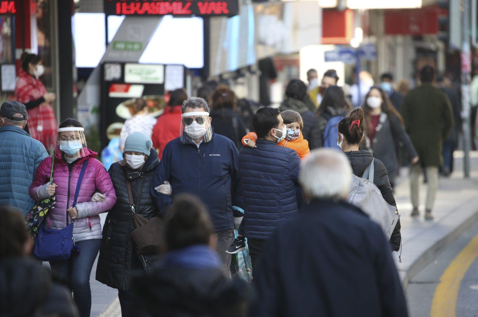 People wearing masks and face shields walk on a street in the capital Ankara, Turkey, Nov. 13, 2020. (AA Photo)