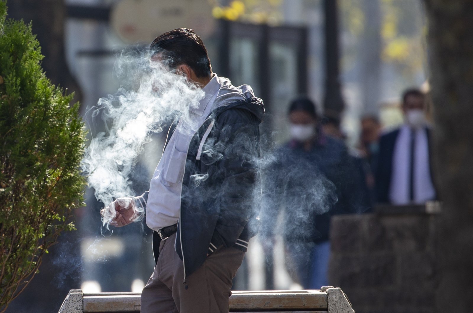 A man with a mask on his chin smokes a cigarette on a street in the capital Ankara, Turkey, Nov. 12, 2020. (AA Photo)