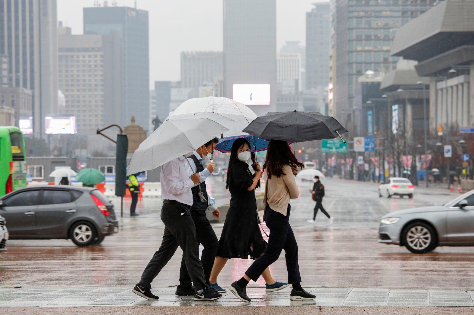 Pedestrians wearing masks walk with umbrellas as it rains amid the coronavirus disease (COVID-19) pandemic in central Seoul, South Korea, November 19, 2020. (Reuters Photo)