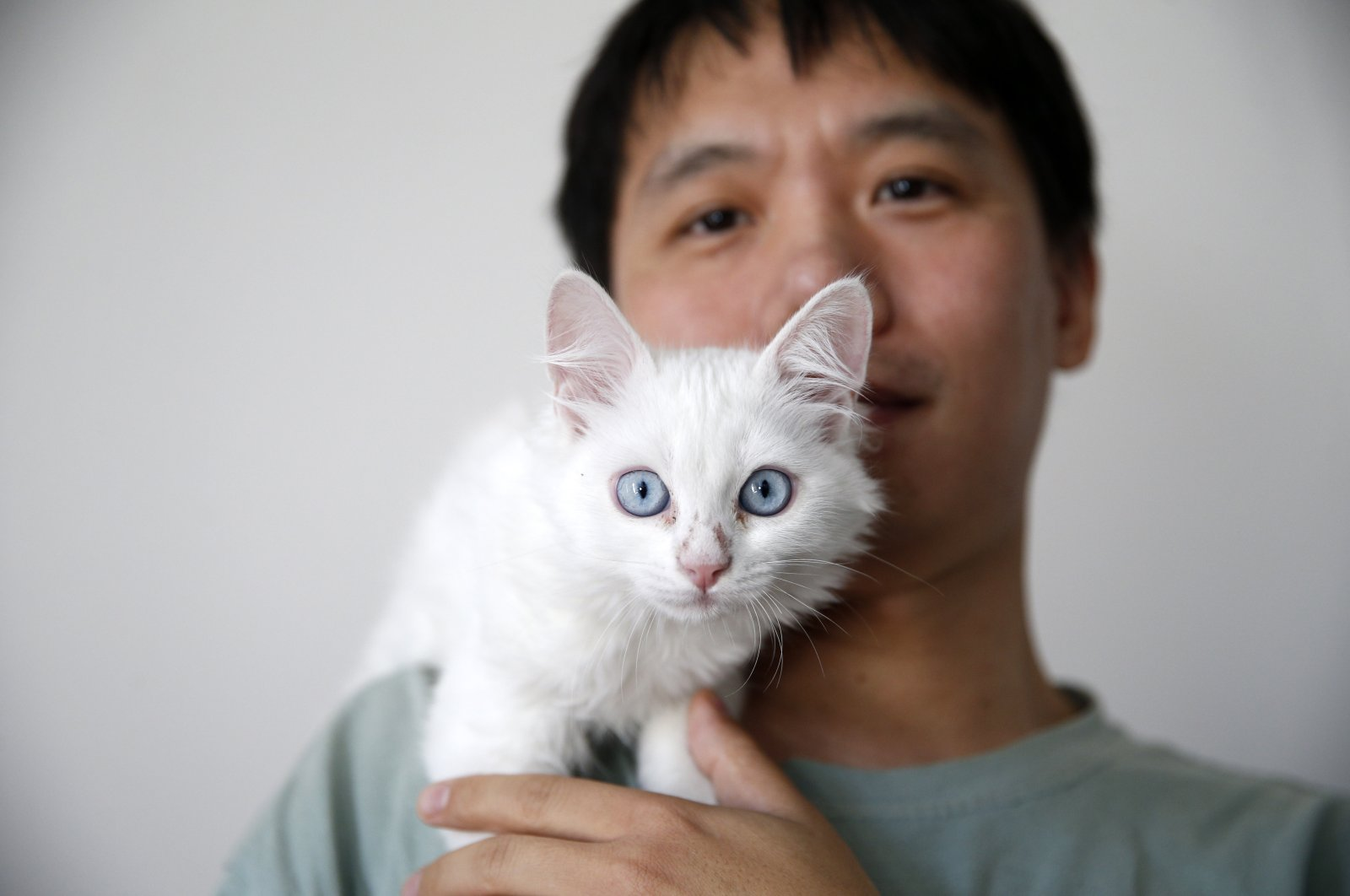 Sun Ping poses with the Van cat he traveled around 7,000 kilometers from China to central Kayseri province to adopt, Turkey, Nov. 18, 2020. (AA Photo)