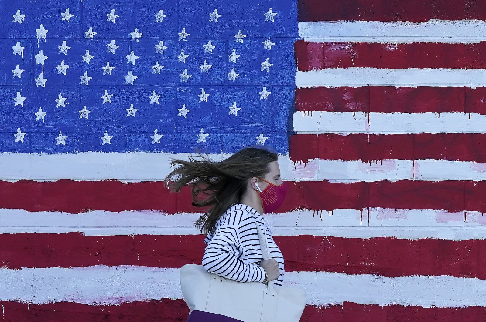 A woman wears a mask while walking past an American flag painted on a wall, San Francisco, California, Nov. 16, 2020. (AP Photo)