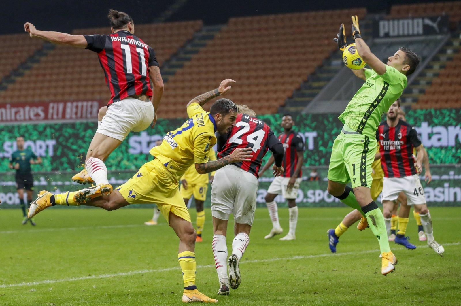 Verona's Marco Silvestri (R) saves as AC Milan's Zlatan Ibrahimovic (L) tries to score during a match, in Milan, Italy, Nov. 8, 2020. (AP Photo)