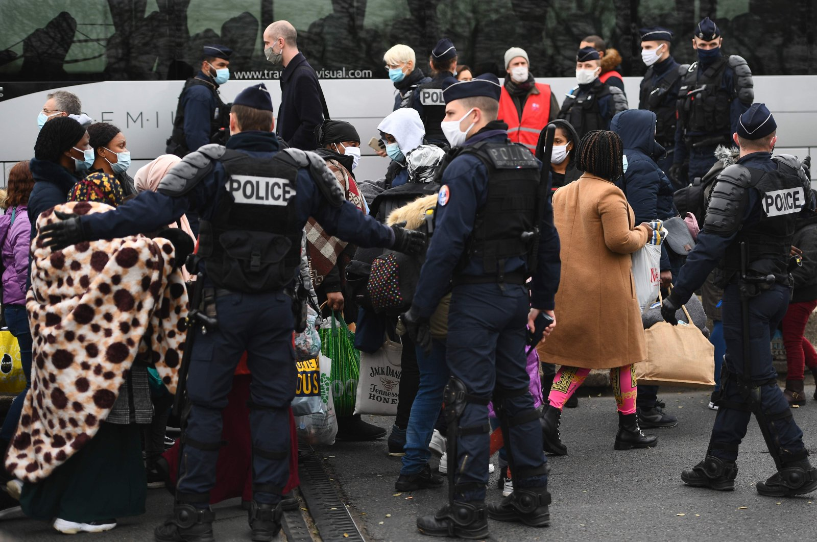 Migrants wait to be taken to shelters after French police raided a makeshift camp set up below the A1 highway in the north of Paris' popular suburb of Saint-Denis, France, Nov. 17, 2020. (AFP Photo)