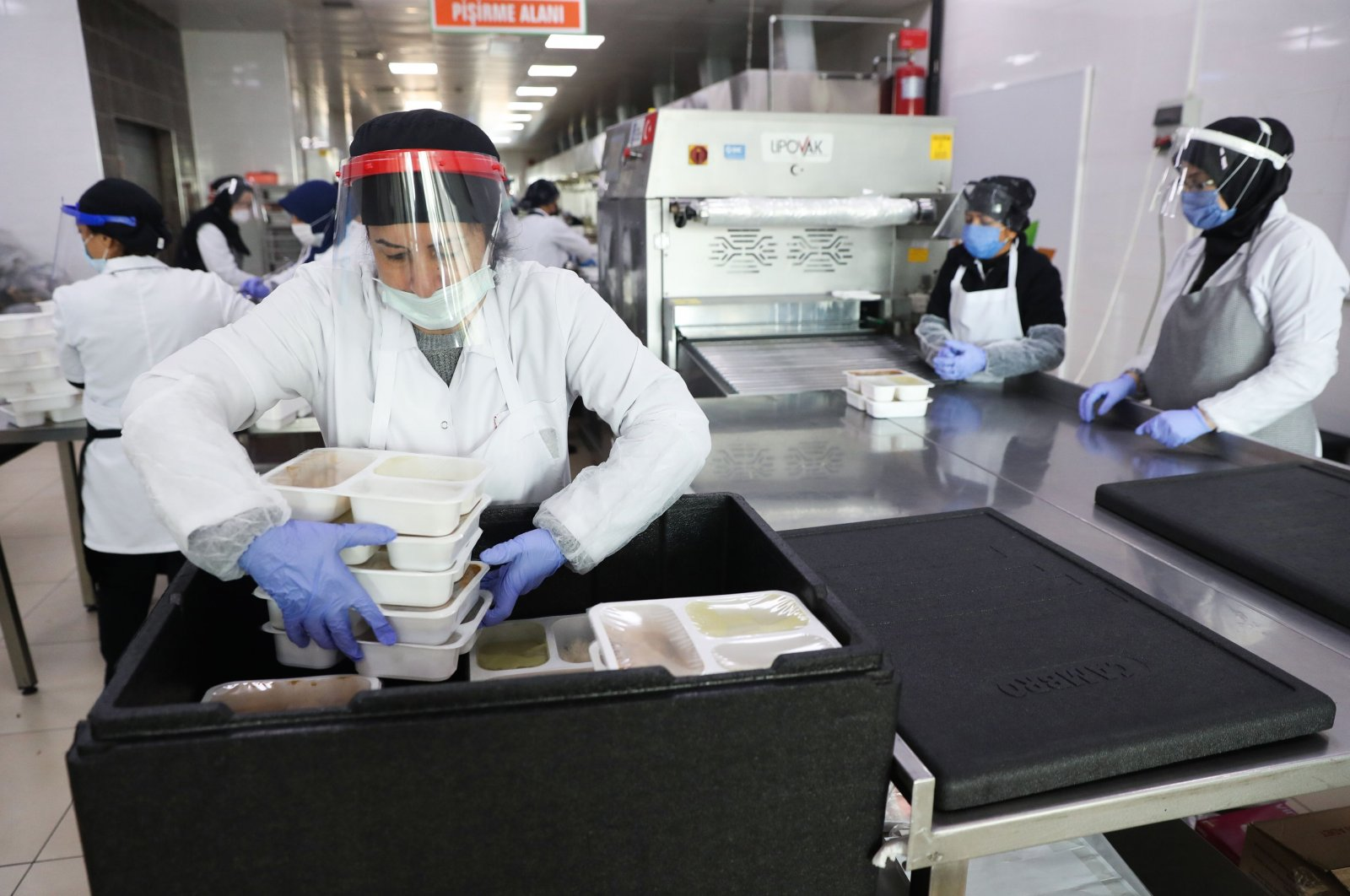 Employees prepare food in the dining production facility at the Ankara Metropolitan Municipality in Ankara, Nov. 19, 2020, as the municipality will provide free breakfast and dinner to people who are forced to quarantine for 15 days because of COVID-19 pandemic, novel coronavirus. (AFP Photo)