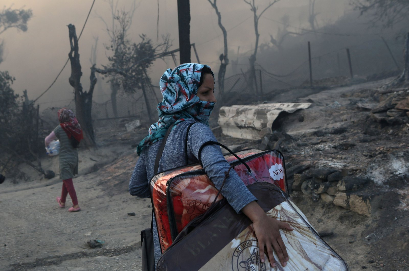 A migrant carries her belongings following a fire at the Moria camp for refugees and migrants on the island of Lesbos, Greece, Sept. 9, 2020. (Reuters Photo)