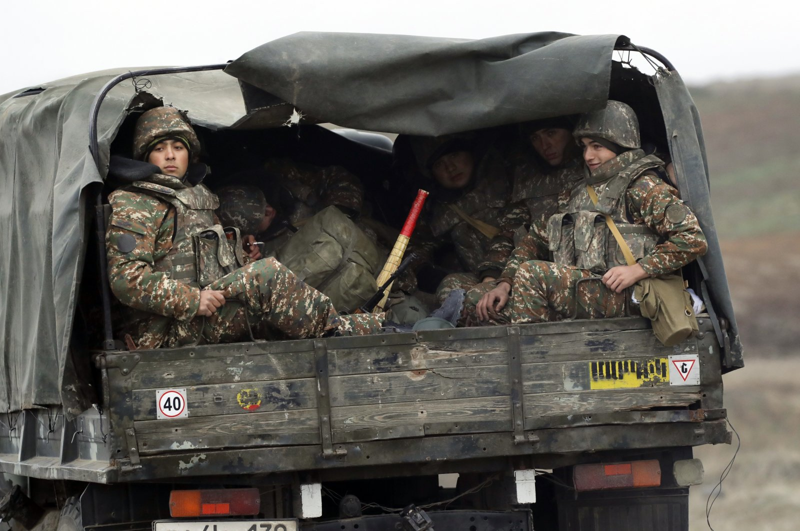 Armenian soldiers sit in a military truck on a road during the withdrawal of Armenian troops from the occupied region of Nagorno-Karabakh, Thursday, Nov. 19, 2020. (AP Photo)