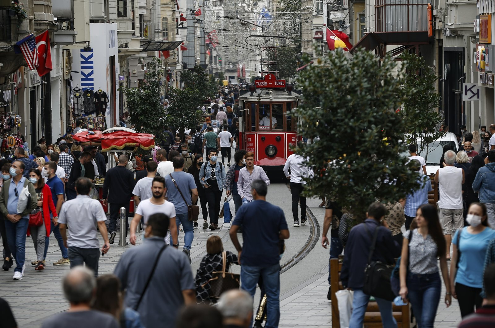 People, most wearing masks to help protect against the spread of the coronavirus, walk along Istiklal Street, the main shopping street in Istanbul, Turkey, Oct. 9, 2020. (AP Photo)