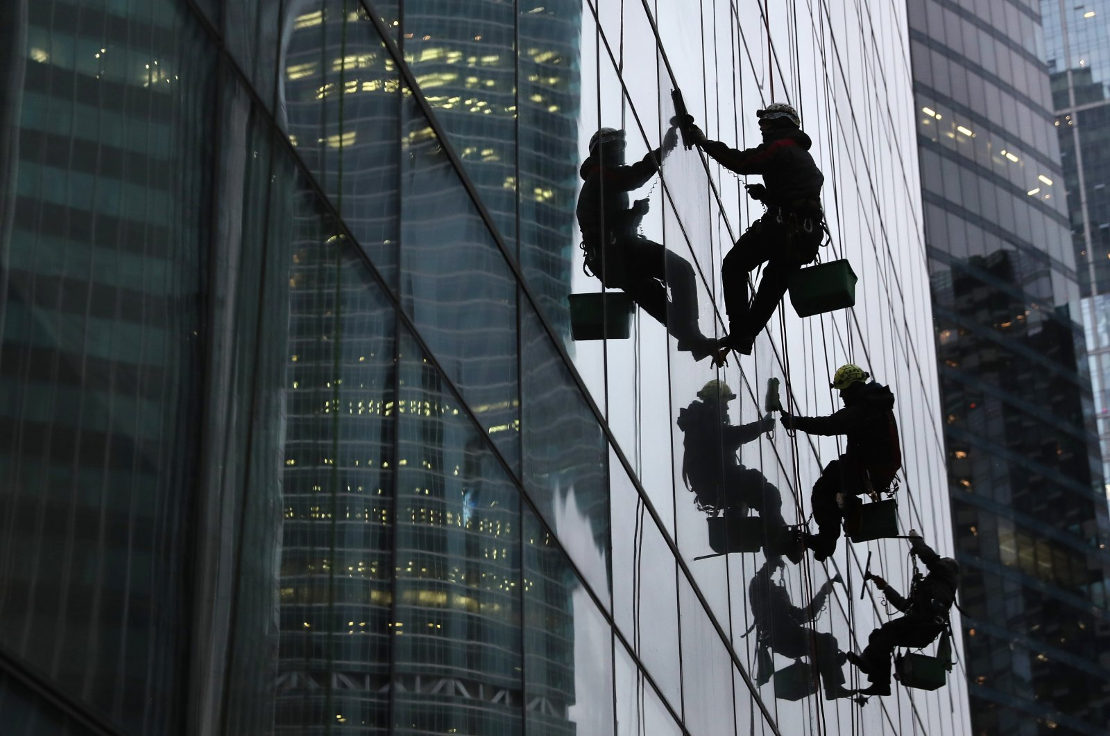 Workers clean the windows of a skyscraper at a business center during the coronavirus pandemic, Moscow, Russia, Nov. 15, 2020. (Photo by Getty Images)