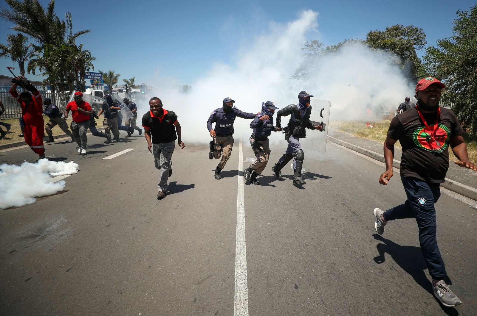 People run away from tear gas during the opposition Economic Freedom Fighters party's protest against alleged racism outside Brackenfell High School, Cape Town, South Africa, Nov. 20, 2020. (Reuters Photo)