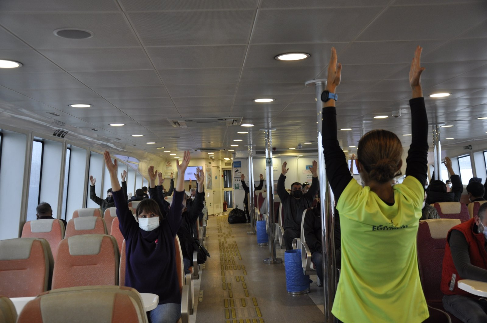 An instructor shows exercise moves to passengers on a ferry, in Istanbul, Turkey, Nov. 20, 2020. (Courtesy of IBB)