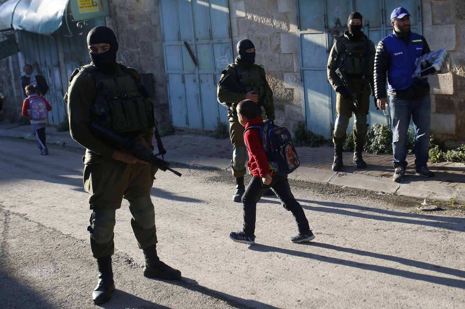 Palestinian children walk past Israeli soldiers on their way to school in the occupied West Bank city of Hebron, Feb. 12, 2019. (AP Photo)