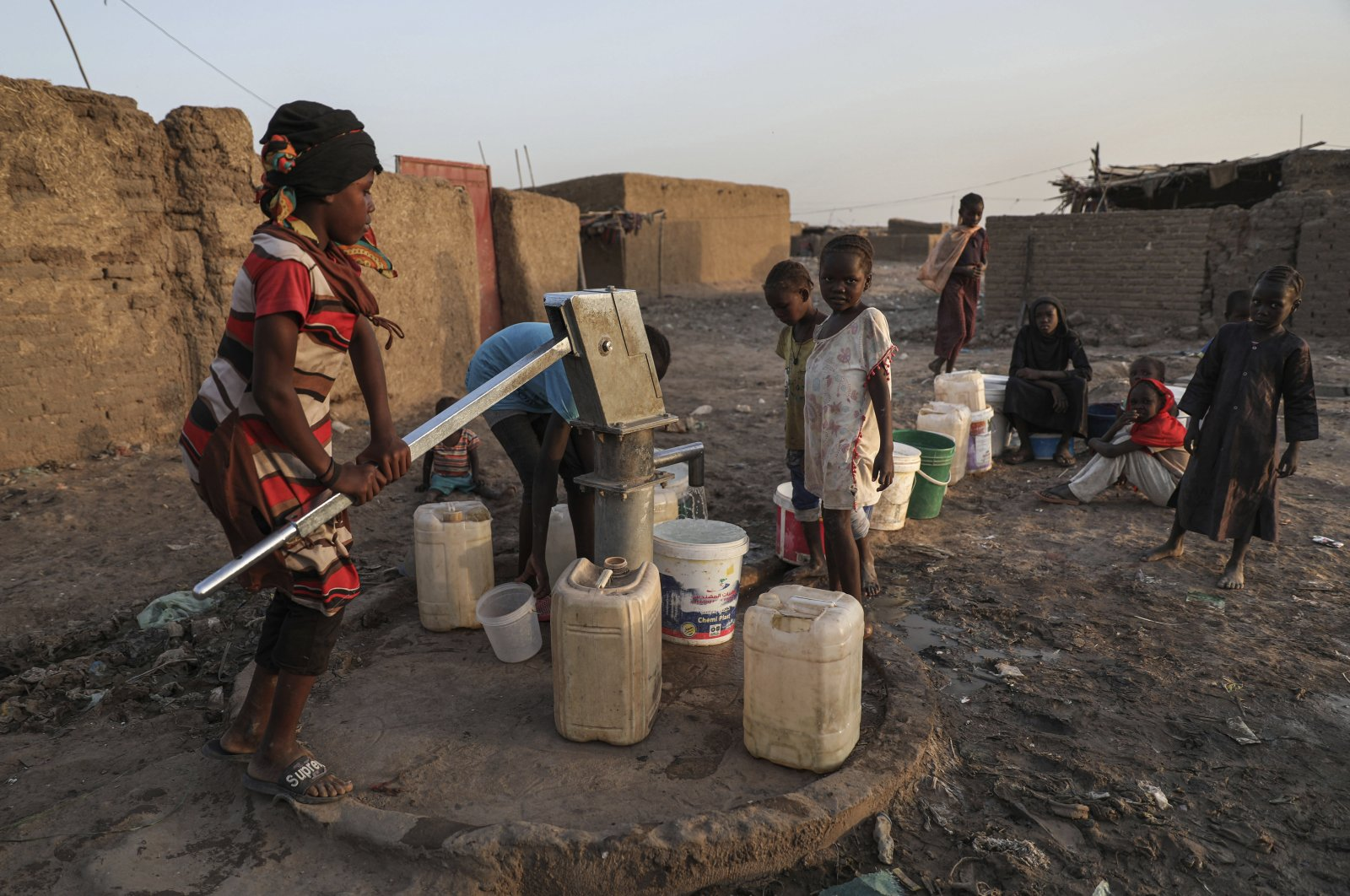 Sudanese girls fill plastic gallons with drinking water from a manual pumping well in May village, about 15 miles from Southern Khartoum, Sudan, Nov. 2, 2020. (AP Photo)