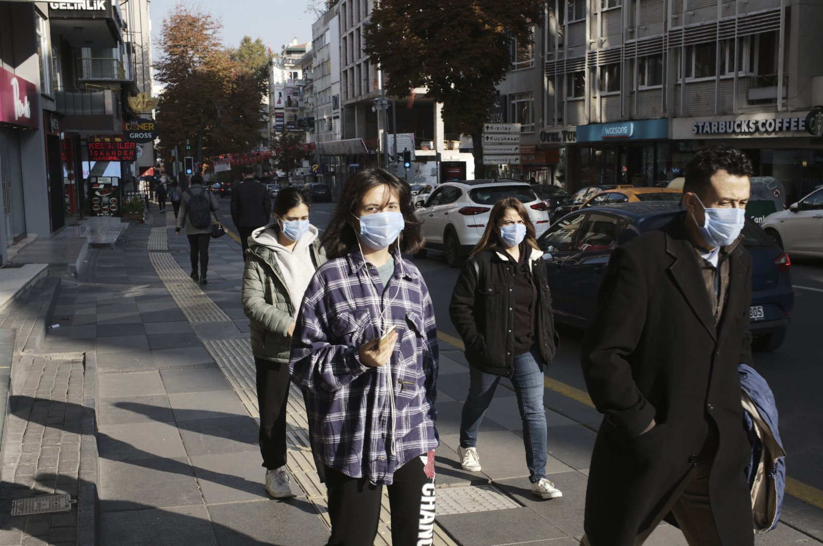 People wearing masks to help protect against the spread of coronavirus, walk, in Ankara, Turkey, Monday, Nov. 15, 2020. (AP Photo)