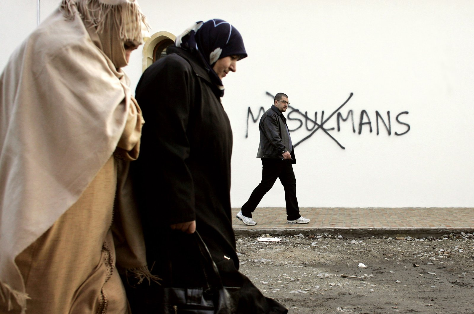 "In this Feb. 8, 2010 file photo, Muslim residents walk past racial slurs painted on the walls of a mosque in the town of Saint-Etienne, central France. Graffiti reads: ""Muslims"". (AP Photo)"