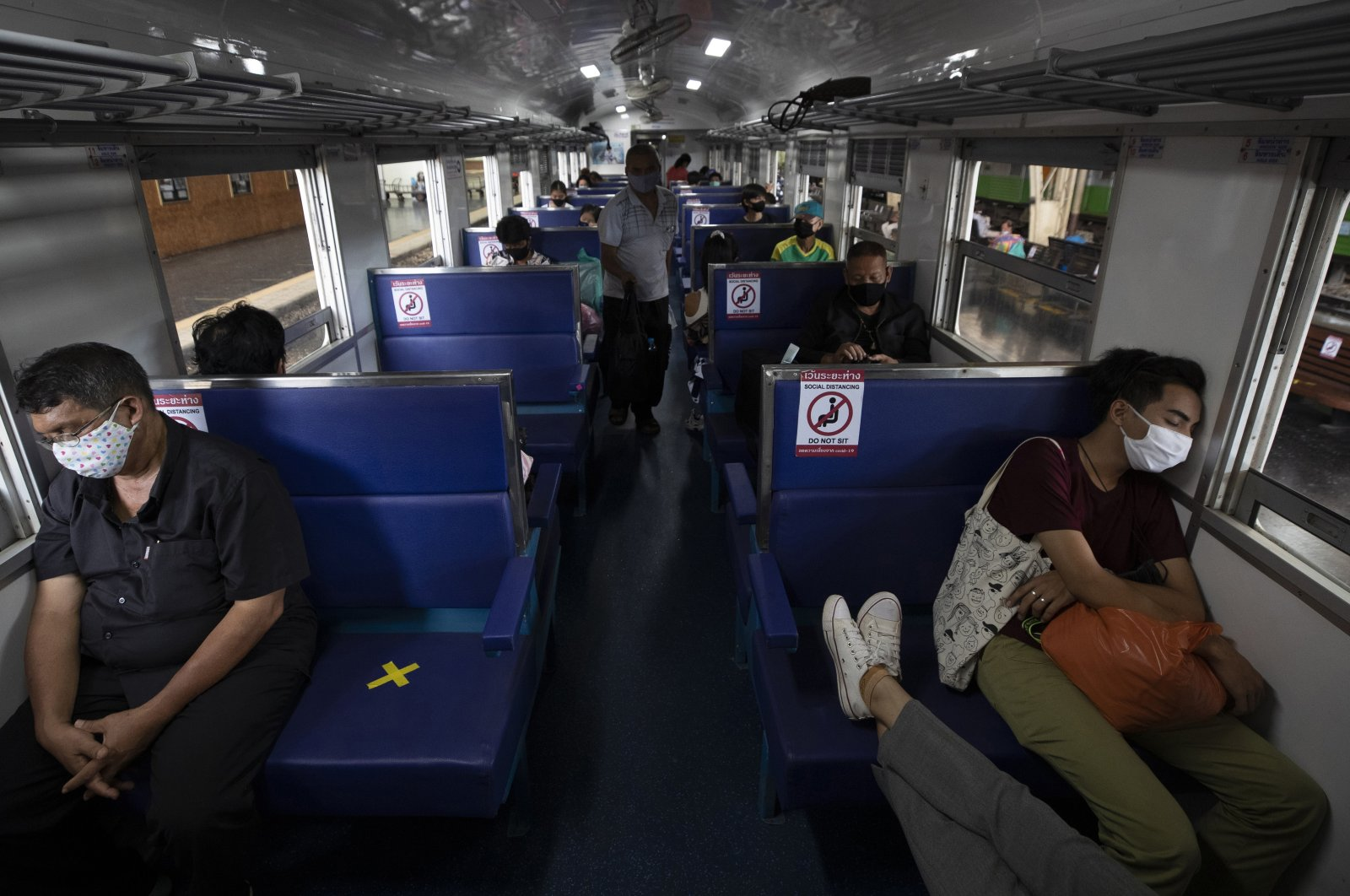 Passengers on a train with staggered seating wear face masks to curb the spread of the coronavirus at the Hua Lamphong Railway Station in Bangkok, Thailand, Tuesday, June 9, 2020. (AP Photo)