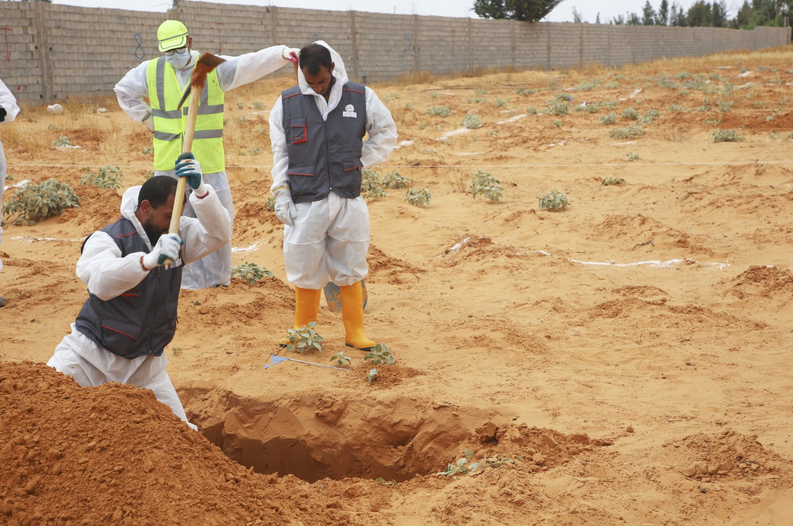 Libyan Ministry of justice employees dig out at a site of a suspected mass grave in the town of Tarhuna, Libya, Tuesday, June 23, 2020. (AP Photo)