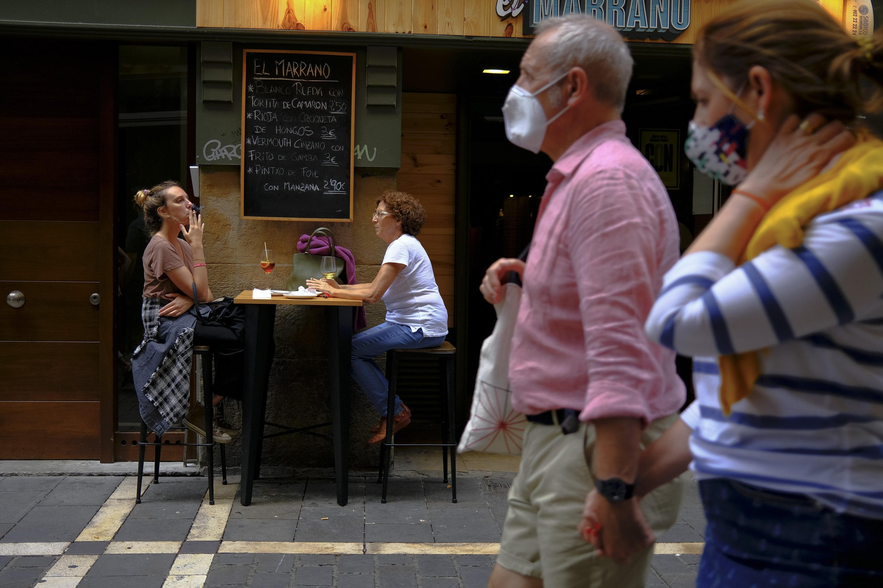Two women smoke cigarettes in a bar while pedestrians wearing face masks walk past, in Pamplona, northern Spain, Aug. 17, 2020. (AP Photo)