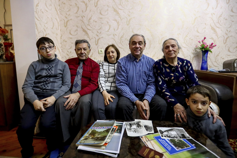 Left to right, Adil Sharifov's grandson Ramazan Sharifov, his uncle Ramiz Humbatov, his sister Kamala Sharifova, Adil Sharifov, his mother Adila Ahmadova and his grandson Tariyel Sharifov pose for a photo at home in Baku, Azerbaijan, Nov. 20, 2020. (AP Photo)