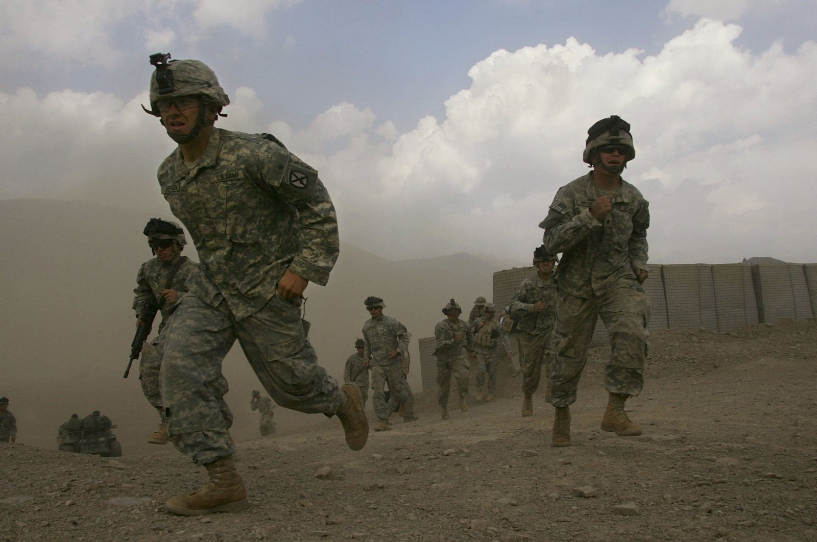 U.S. soldiers run to quickly unload a supply helicopter between Taliban rocket attacks, at Camp Tillman in the Paktika province of eastern Afghanistan, Oct. 24, 2006. (Photo by Getty Images)