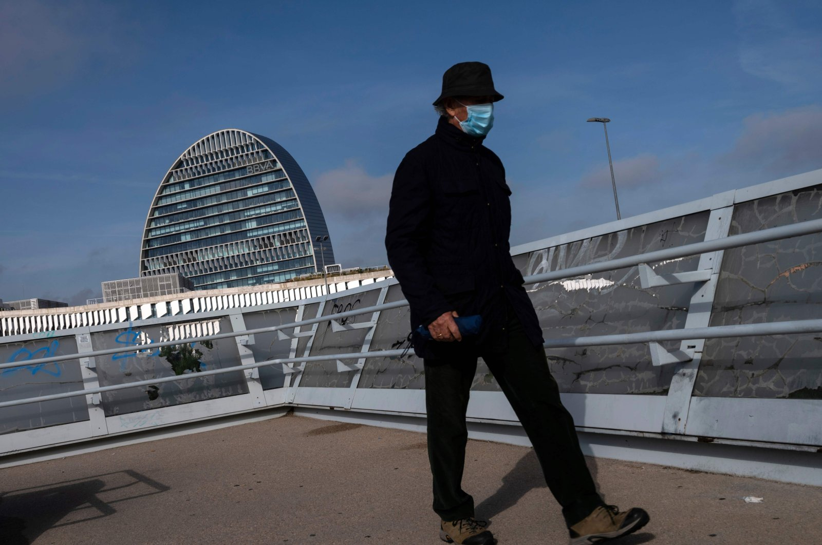 A man wearing a mask walks with La Vela (The Sail) building in the background, housing the head office of Spanish bank BBVA (Bilbao Vizcaya Argentaria Bank) in Madrid, Nov. 16, 2020. (AFP Photo)
