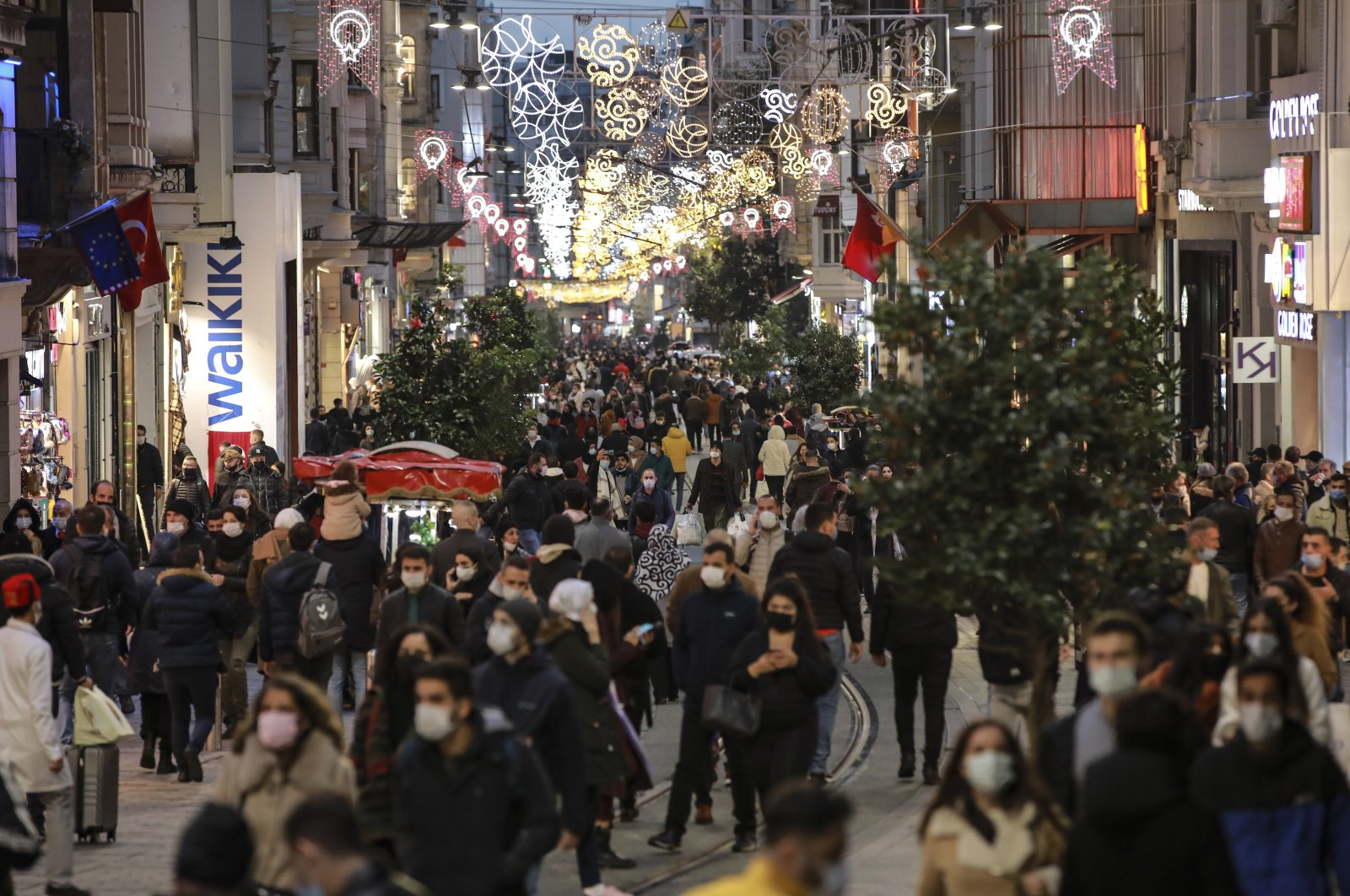 People wearing protective masks walk along Istiklal Avenue, in Istanbul, Turkey, Nov. 21, 2020. (AP Photo)