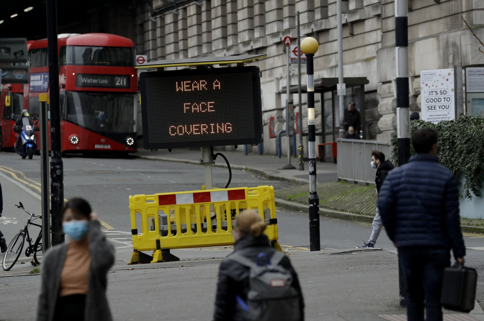 A sign is displayed outside Waterloo train station to remind people they are required to wear face coverings inside the station and while traveling on trains during England's second coronavirus lockdown, in London, Nov. 20, 2020. (AP Photo)