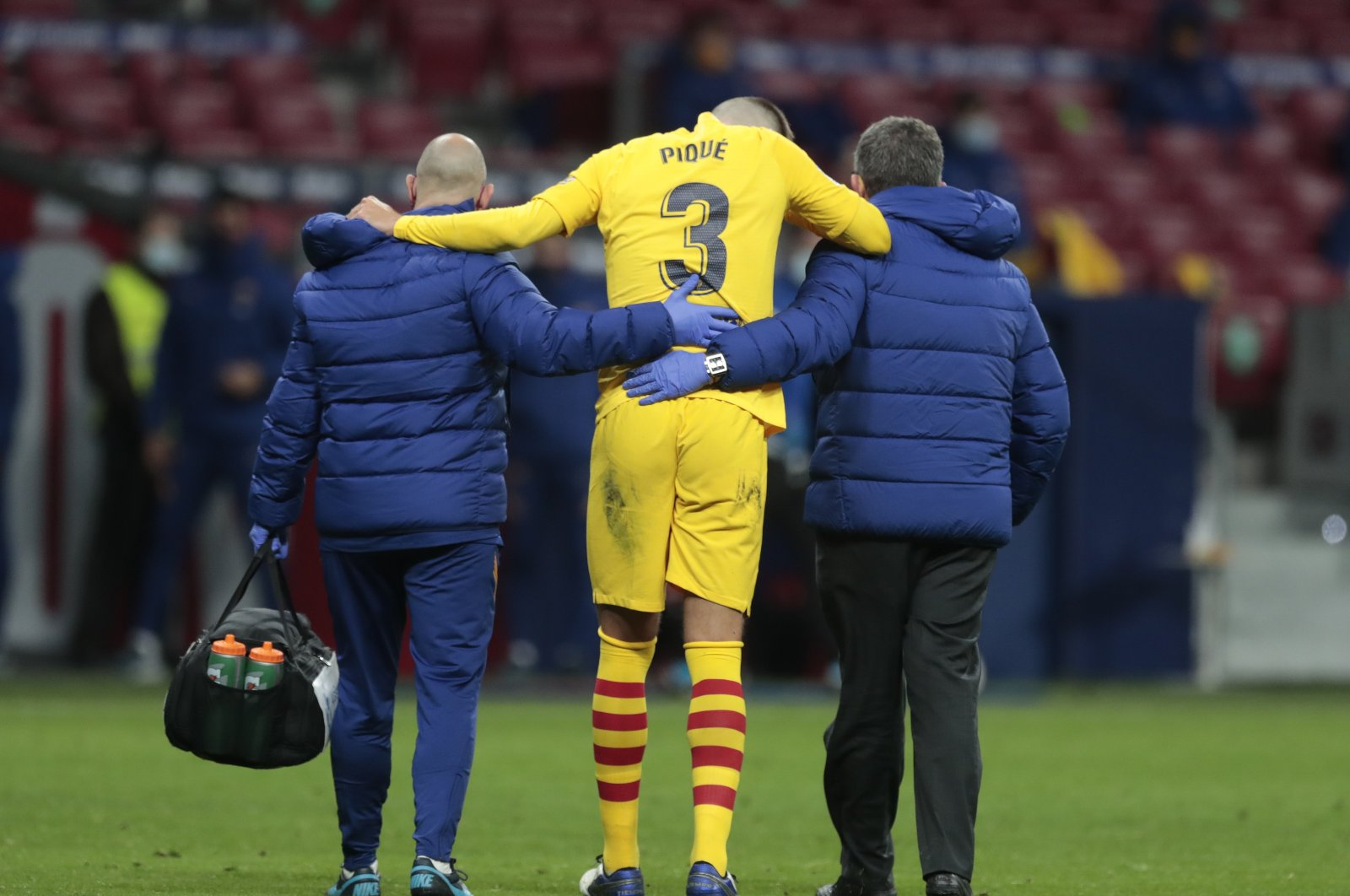 Barcelona's Gerard Pique is assisted off the pitch after getting injured, Madrid, Spain, Nov. 21, 2020. (AP Photo)