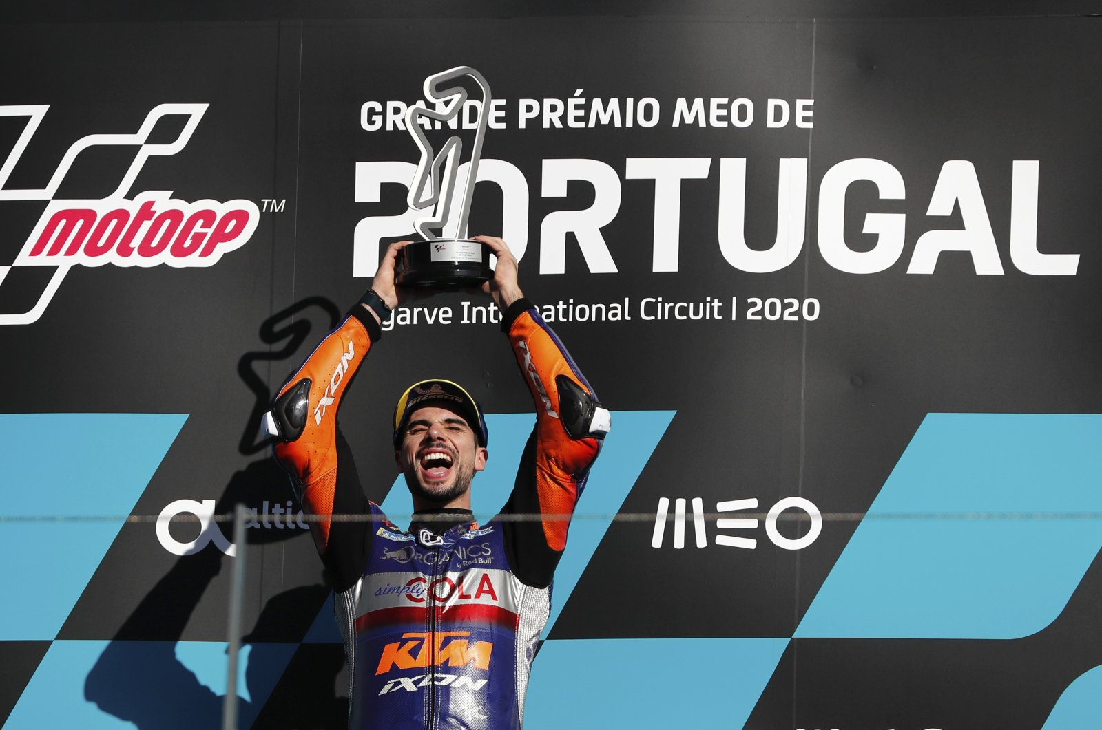 MotoGP rider Miguel Oliveira of Portugal celebrates on the podium after winning the MotoGP race of the Portuguese Motorcycle Grand Prix, the last race of the season, at the Algarve International Circuit near Portimao, Portugal, Nov. 22, 2020. (AP Photo)