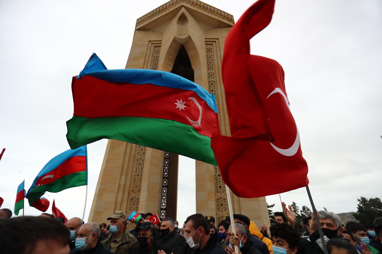 Azerbaijanis wave national flags as they celebrate the entry of Azerbaijani troops into Nagorno-Karabakh's Aghdam region in Baku, Azerbaijan, Nov. 20, 2020. (AP)