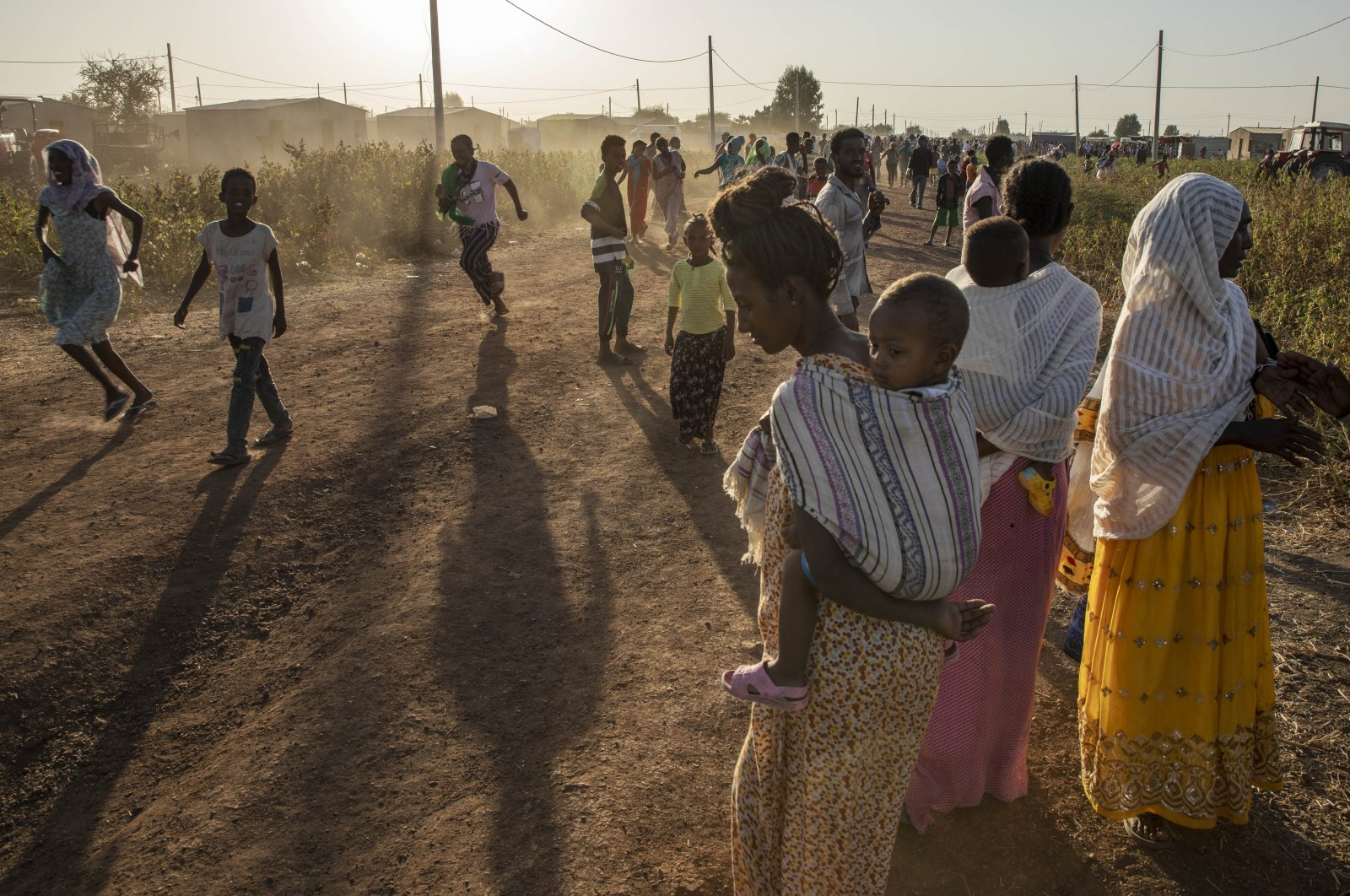 Tigray refugees who fled a conflict in Ethiopia's Tigray region run at Village 8, the transit center near the Lugdi border crossing, eastern Sudan, Nov. 22, 2020. (AP Photo)