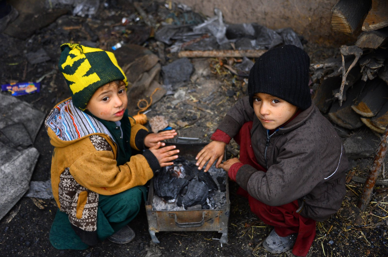 Children warm up around a charcoal fire, in Herat, Afghanistan, Nov. 22, 2020. (AFP Photo)